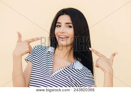 Indoor Shot Of Good Looking Young Female Indicates At Her Mouth With Smile, Had Long Dark Hair, Show