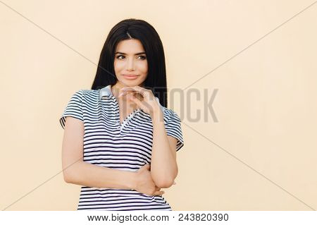 Waist Up Portrait Of Thoughtful Female With Dark Straight Long Hair, Keeps Hand Under Chin, Contempl