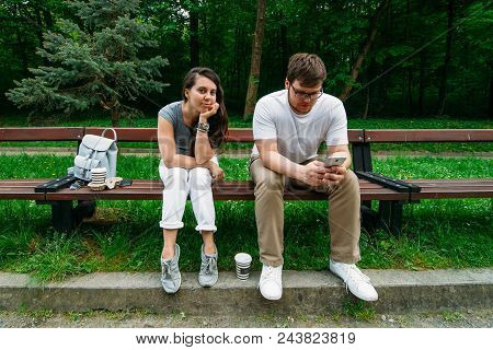 Couple Sitting On Bench In City Park. Woman Is Boring, Man Looking Into Smartphone.