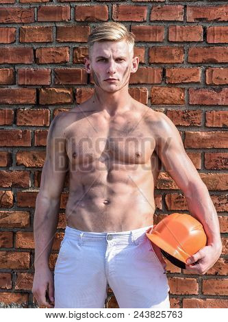 Builder With Muscular Torso And Helmet, Brick Wall On Background. Athlete With Sexy Nude Torso With