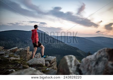 Man Celebrating Sunset Looking At View In Mountains. Trail Runner, Hiker Or Climber Reached Top Of A
