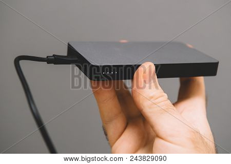 Man Holding Against Gray Background A Power Bank For Charging Mobile Devices Also Know As External B