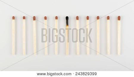 One Burned Match Among Many Unburned Ones. Group Of Match Sticks Or Safety Matches. Individuality An