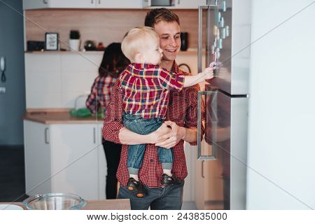 Dad And Little Son In The Kitchen By The Fridge, Posing On The Camera