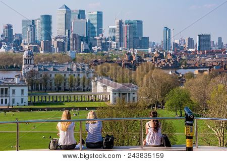 London, United Kingdom - April 20: People Sitting At The Top Of The Hill In Greenwich Park Viewing T