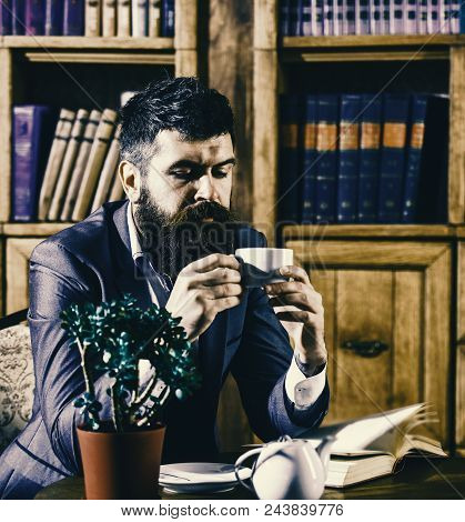 librarian to the library. Oldfashioned man holds cup with tea. Aristocratic lifestyle concept. Aristocrat on thoughtful face having tea. Man in classic suit sits in vintage interior, library, book shelves on background. poster