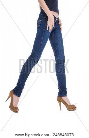 Woman legs in denim trousers high heels shoes posing in studio