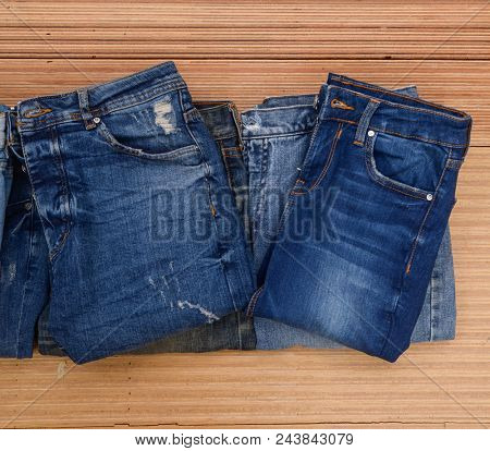 Pile of blue jeans on wooden.board
