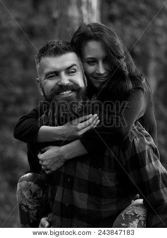 Couple In Love. Man Carrying His Happy Girlfriend On Back, Woman With Smiling Face Hugs Her Boyfrien