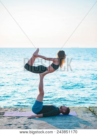 Young Beautiful Couple Practicing Acro Yoga On The Sea Beach Near Water. Man And Woman Doing Everyda