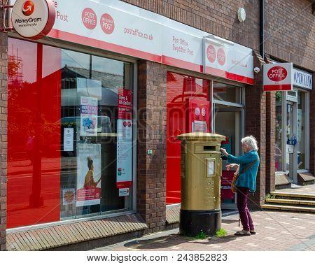 Flint, Uk: June 4, 2018: An Elderly Woman Posts Some Letters In A Post Box Outside Flint Post Office