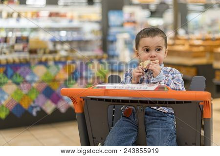 Cute Boy Eating A Bun Or Pita Bread In A Supermarket In The Cart. Hungry Child In The Store. Toddler