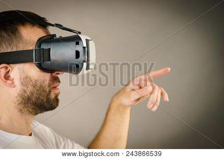 Adult Short Bearded Guy Exploring Virtual Reality Wearing Vr Goggles Being Into Technology Pointing