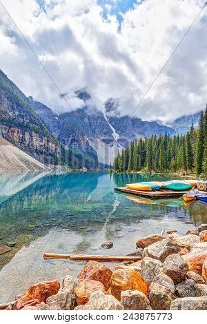 Reflective Moraine Lake At Lake Louise Near Banff In The Canadian Rockies, With Canoes Nearby And He