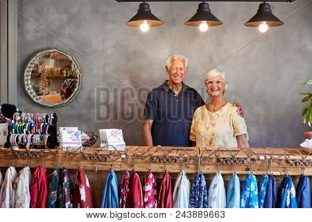 Portrait Of Senior Store Owners Standing Behind Cash Desk