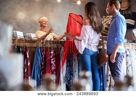 Store Owner Standing Behind Cash Desk Serving Customers