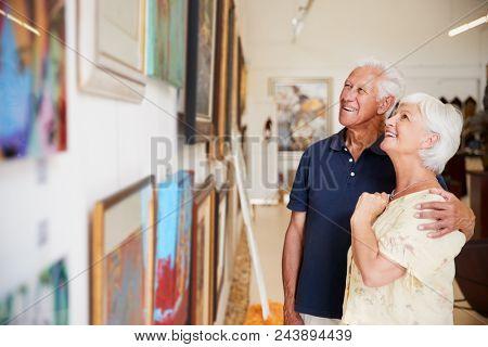 Senior Couple Looking At Paintings In Art Gallery