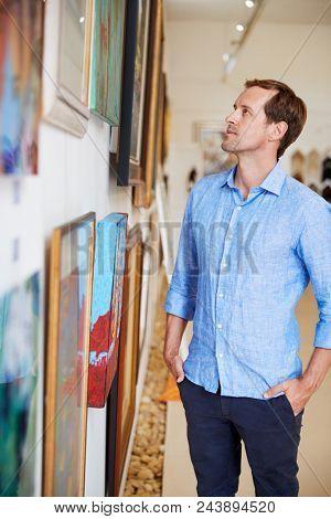 Man Looking At Paintings In Art Gallery