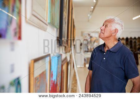 Senior Man Looking At Paintings In Art Gallery