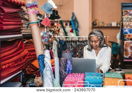 Smiling Mature Fabric Shop Owner Working On A Laptop While Standing At A Counter Surrounded By Color