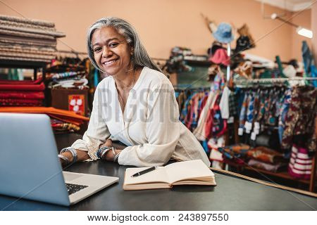 Portrait Of A Smiling Mature Fabric Shop Owner Working On A Laptop And Writing Down Notes At Her Sto