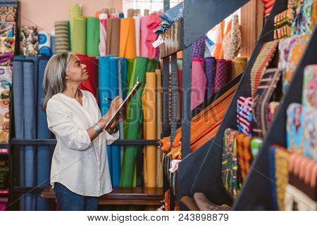 Mature Fabric Store Owner Standing In Her Shop Surrounded By Colorful Cloths And Textiles Taking Inv