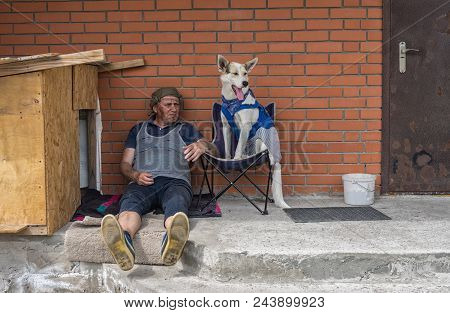 Dirty Dressed Mature Man Sitting Near Brick Wall While Dog In Casual Clothes   Resting In A Chair Ne