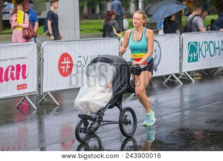 Dnipro, Ukraine - May 20, 2017: Young Woman Running With Baby Carriage  During Of The Interipe  Dnip