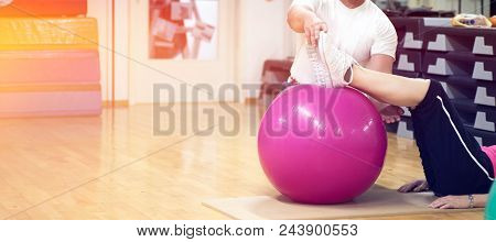 Exercising With Personal Trainer On Large Stability Ball In Studio Fitness Back Physiotherapy