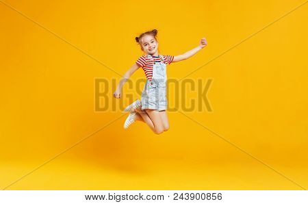 Funny Child Girl Jumping On A Colored Yellow Background