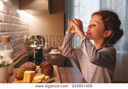 Child Girl Is Drinking Water In The Kitchen At Home