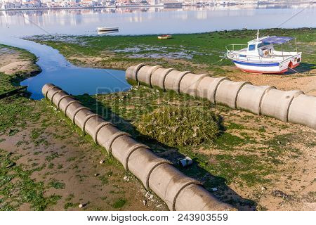 Two open air sewer pipes draining to the Seixal Bay, a Tagus River branch near Lisbon, Portugal.
