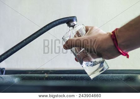 Closeup Shot Of A Man Pouring A Glass Of Raw Unfiltered Drinking Water From A Kitchen Tap. A Man Pou