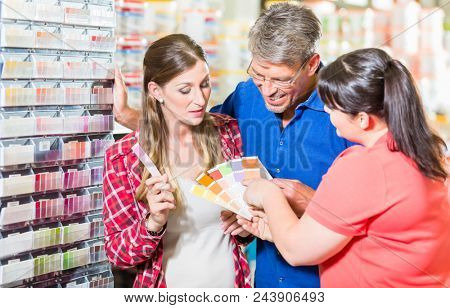 Home improvement store clerk counseling customers about choice of colour for wall paint