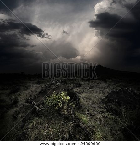 Dark clouds over volcanic valley with grass and rocks. Mountain Agung in Bali. Indonesia