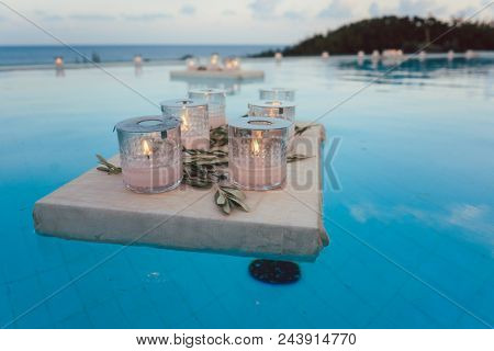 Candles floating in swimming pool at beach house party as decoration