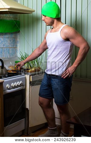 Fitness Man Cooking. Healthy Strong Muscular Sport Man Standing On Kitchen And Cooking. Strong Sport