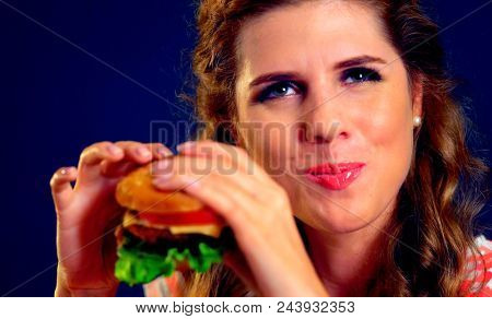 Woman eating sandwich. Girl with pleasure eats burger after diet. She opened her mouth, holding a hamburger on his outstretched hands and closed her eyes. Girl must be feminine.