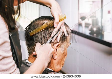 An elderly man in hairdressing salon. Hairdresser makes a stylish haircut for an elderly man. Hairdo for grandpa poster