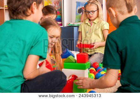 Children building blocks in kindergarten. Group kids playing toy on floor. Top view of interior preschool. Mat is big construction site building tower of cubes. Tournament of children's creativity.