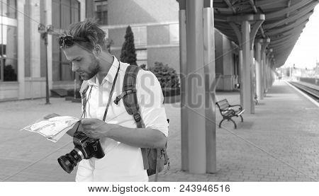 Tourist Walks. Travelling And Navigation Concept. Tourists On Train Station Looking At A Guide. Trav