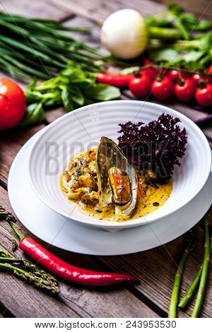 Mussel Cooking With Lemon And Herbs In Clay Pot Over Wood Background A