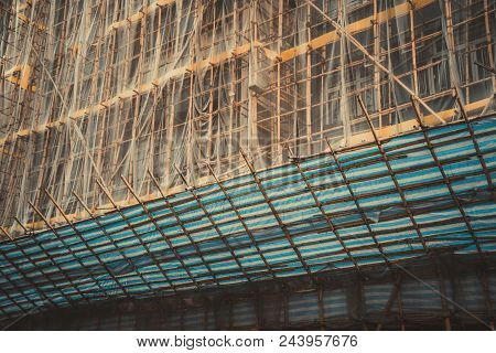 Traditional Bamboo Scaffolding And Shading Net Setup For Paint And Instruction Building. Asian Scaff