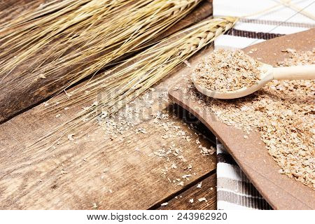 Plate And Wooden Spoon Filled With Wheat Bran Next To Wheat Ears On Wood Table. Healthy Eating Conce