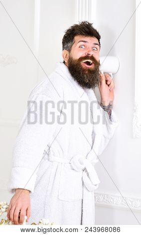 Hipster in bathrobe on surprised face secretly listen conversation. Secret and spy concept. Man with beard and mustache eavesdrops using mug near wall. Man in white interior spying, eavesdropping. poster