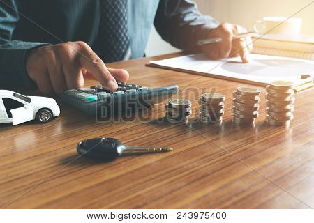 Business Man Putting Calculator To Calculate His Account In Office For Saving,financial,with Car Toy