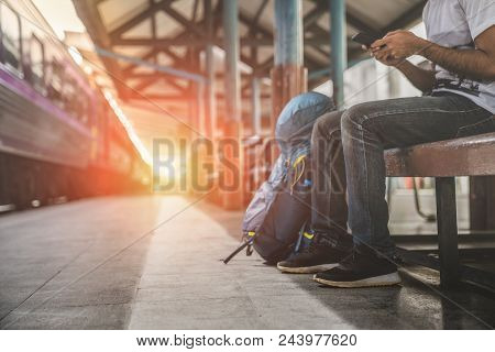 Backpack And Hat At The Train Station With A Traveler, Young Man Sitting With Using Smartphone At Th