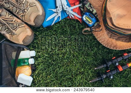 Hiking Set . Travel Equipment And Accessories For Travel And Hiking Trip On Green Grass, Top View, F
