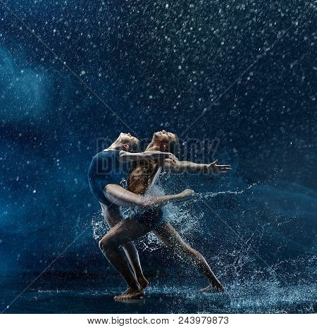 Young Couple Of Ballet Dancers Dancing Under Water Splash And Drops. Young Caucasian And Afro Americ