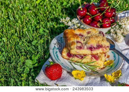 Portion Of Cherry Cake With Ripe Strawberries Around And Few Yellow Blooms